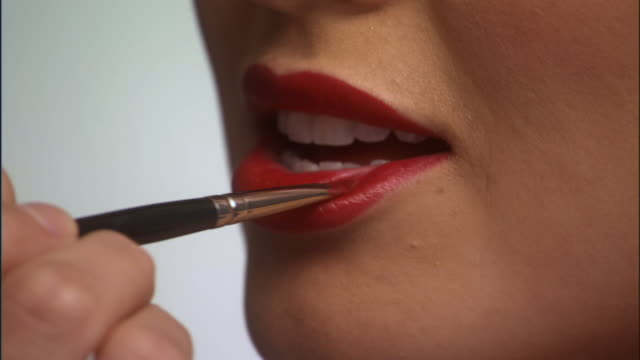 slo mo, ecu, young woman applying red lipstick with make-up brush - applying stock videos and b-roll footage