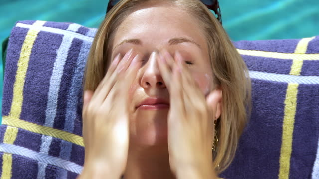 cu young woman applying sun cream on face on poolside / sherman oaks, california, usa.  - sun cream stock videos & royalty-free footage