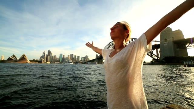 Junge Frau Arme ausgestreckt im Hafen von Sydney