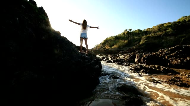 Young woman arms outstretched on steep rock at sunrise