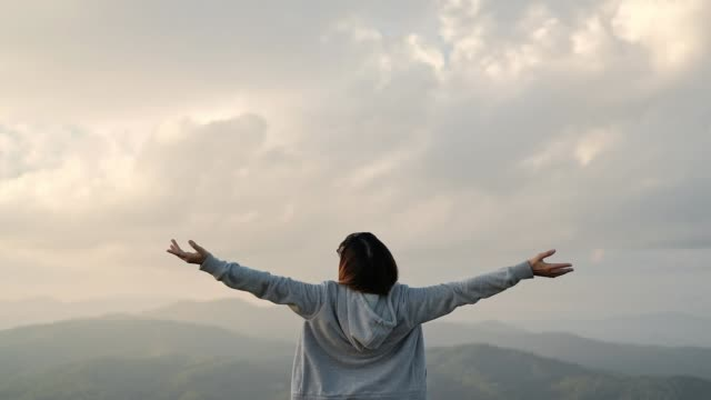 young woman arms outstretched relaxation and freedom on top mountain - wishing stock videos & royalty-free footage