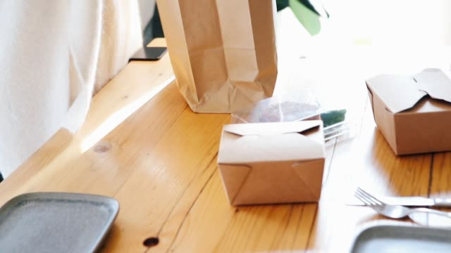 young woman arranging takeaway food on the table, getting ready for lunch - paper bag stock videos & royalty-free footage