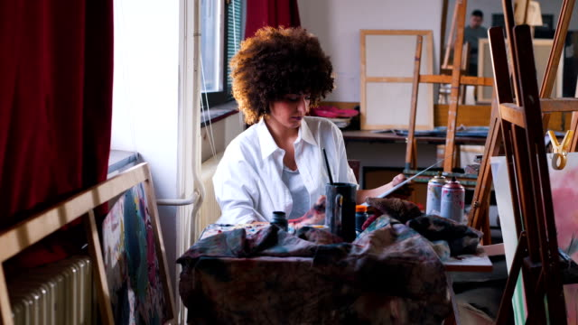 young woman artist painting in her studio - hobby video stock e b–roll