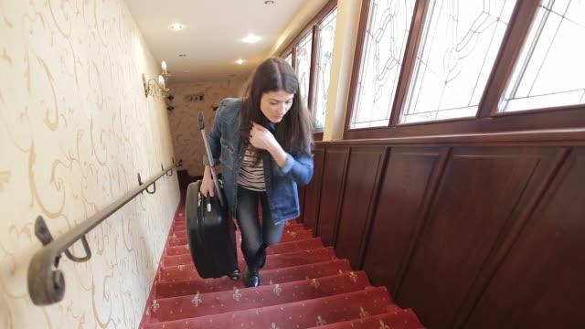 vídeos y material grabado en eventos de stock de mujer joven sobre las escaleras en el hotel. - alojamiento y desayuno