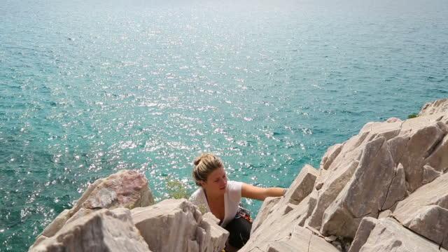 Young woman ascends Mediterranean sea cliff