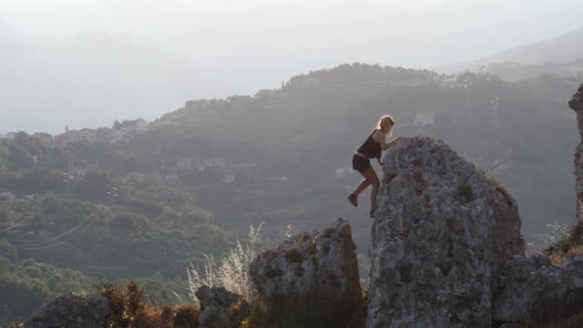 Young woman ascends rock ridge, above hills, valley