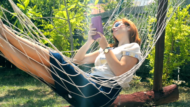 Young woman at 30s relaxing on the hammock II