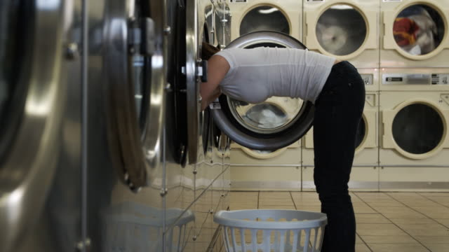 young woman at a laundromat - wäschekorb stock-videos und b-roll-filmmaterial
