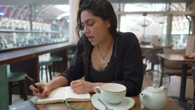 a young woman at a table in a cafe. - diary stock videos & royalty-free footage