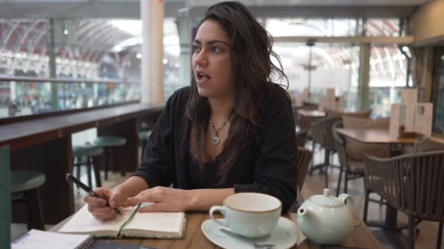 a young woman at a table in a cafe. - poetry stock videos & royalty-free footage