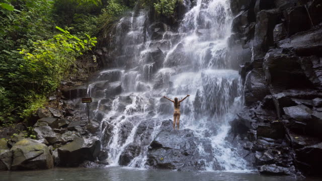 young woman at a waterfall with her arms outstretched - forearm stock videos and b-roll footage