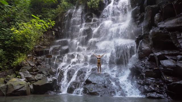 Jonge vrouw bij een waterval met haar uitgestrekte armen