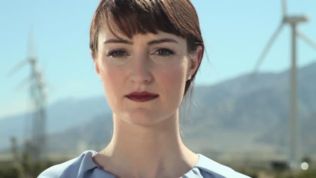 vidéos et rushes de young woman at a wind farm - tête composition