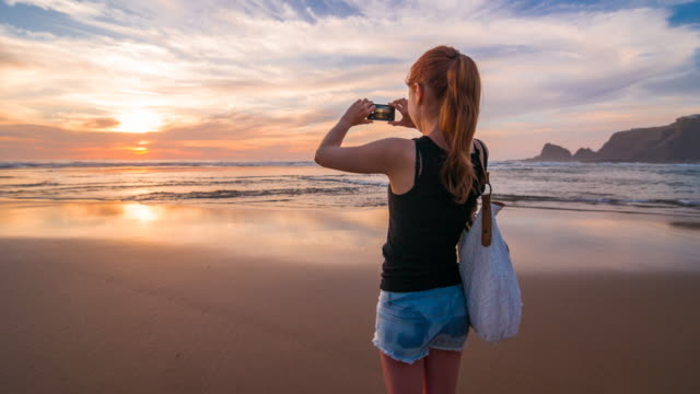 Young woman at beach taking pictures of sunset with phone