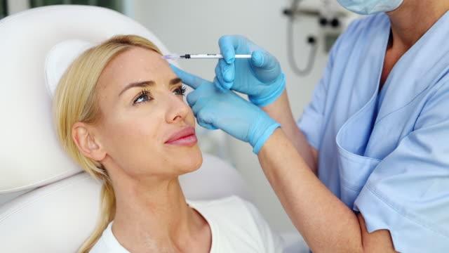 giovane donna alla clinica di trattamento della bellezza - labbra video stock e b–roll