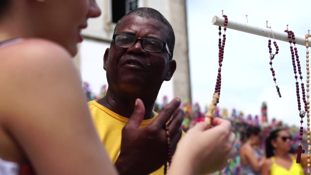 young woman at buying crucifix at street market - recife stock videos and b-roll footage