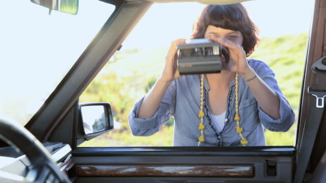 young woman at car door taking instant photograph and laughing - shaking stock-videos und b-roll-filmmaterial