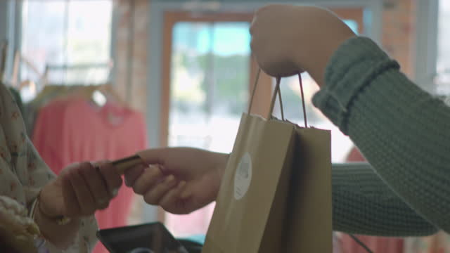 Young woman at checkout takes credit card and shopping bag from cashier at hip downtown shop.