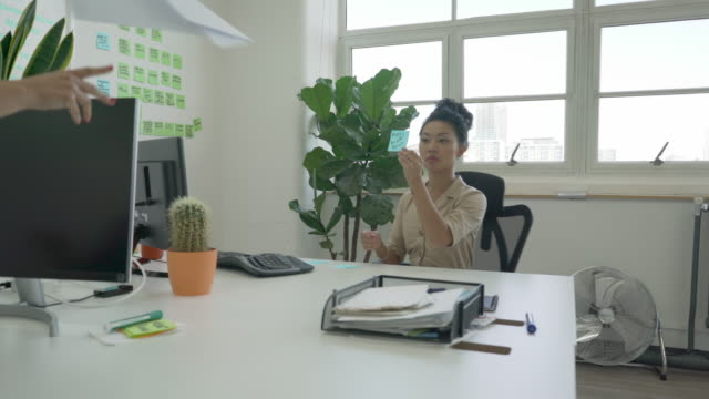 """vídeos de stock, filmes e b-roll de a young woman at her desk in an office holds up a post it note saying """"why do we exist"""" - gaivota"""