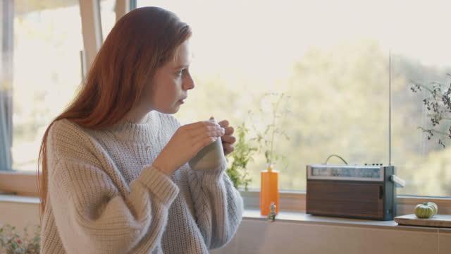 vídeos y material grabado en eventos de stock de young woman at home drinking tea looking out of window - mirar por la ventana