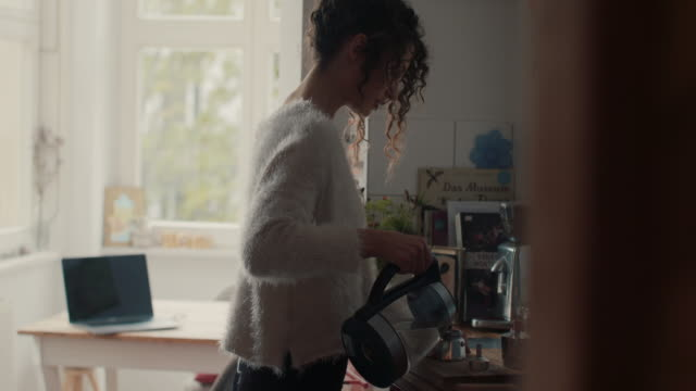 vidéos et rushes de young woman at home in berlin making coffee - préparation