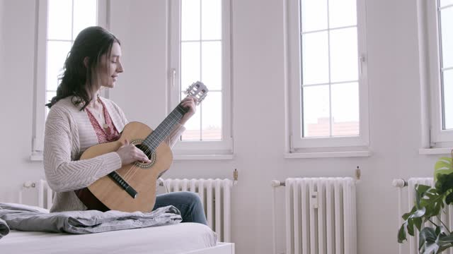 young woman at home learning to play the guitar - weekend activities stock videos & royalty-free footage