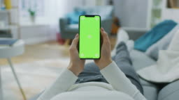 Young Woman at Home Lying on a Couch using with Green Mock-up Screen Smartphone. Girl Using Mobile Phone, Browsing through Internet, Watching Content, Chatting in Social Networks with Friends. POV.