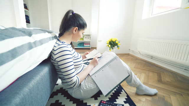 young woman at home studying. - note pad video stock e b–roll