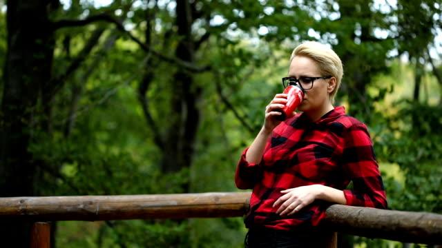 vídeos de stock e filmes b-roll de young woman at home terrace sipping coffee from a cup - cabana estrutura construída