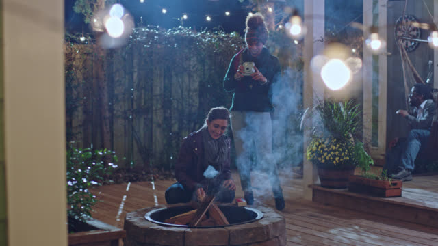 Young woman at house party takes photo with camera as smoke rises from fire pit.
