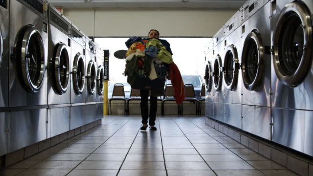young woman at laundromat - waschsalon stock-videos und b-roll-filmmaterial