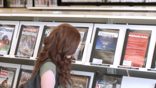 vidéos et rushes de ms pan young woman at magazine display rack at public library flips open a magazine while older woman in next aisle browses magazines displayed on racks / rancho mirage, california, usa - magazine