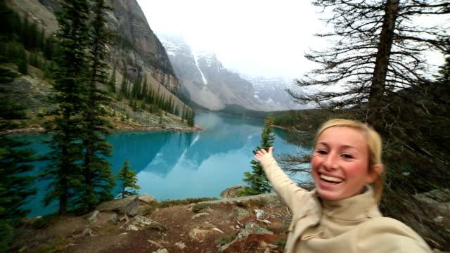 Ung kvinna på Moraine lake tar en selfie porträtt