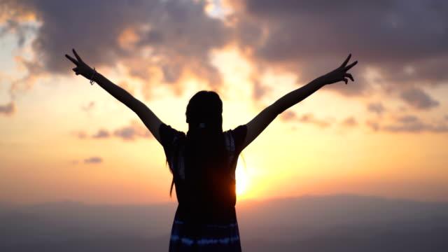 stockvideo's en b-roll-footage met de jonge vrouw bij de zonsondergang van de bergtop maak v teken - geloof
