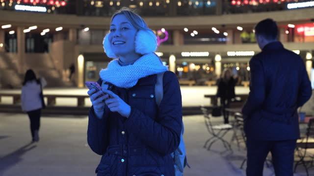vídeos de stock, filmes e b-roll de a young woman at night in winter using her mobile phone. - protetor de ouvido