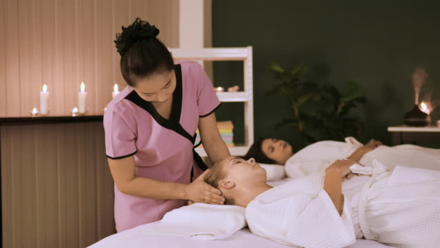 young woman at spa receiving head massage. - head massage stock videos & royalty-free footage
