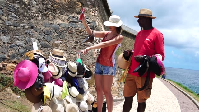 young woman at street market choosing hat - bahia state stock videos & royalty-free footage