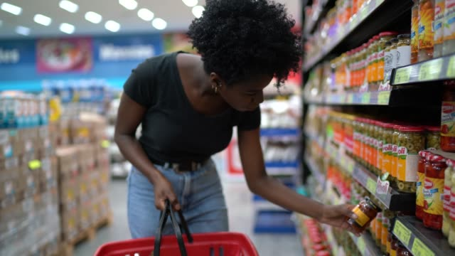 young woman at supermarket shelf - supermarket stock videos & royalty-free footage
