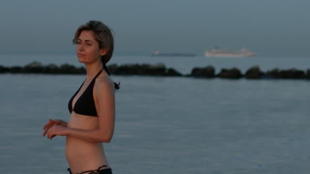 a young woman at the beach at sunrise - 美しい人点の映像素材/bロール