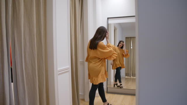 ung kvinna i omklädningsrummet på en klädaffär som försöker på en gul casual klänning - omklädningsrum bildbanksvideor och videomaterial från bakom kulisserna