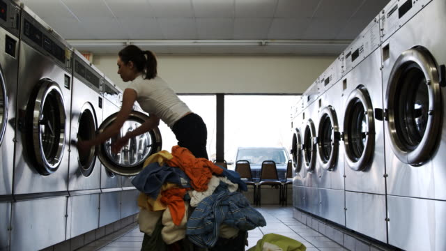 young woman at the laundromat - waschsalon stock-videos und b-roll-filmmaterial