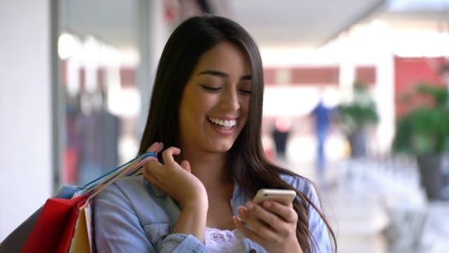 vídeos de stock, filmes e b-roll de jovem mulher no shopping bate-papo online usando seu smartphone rindo - e commerce