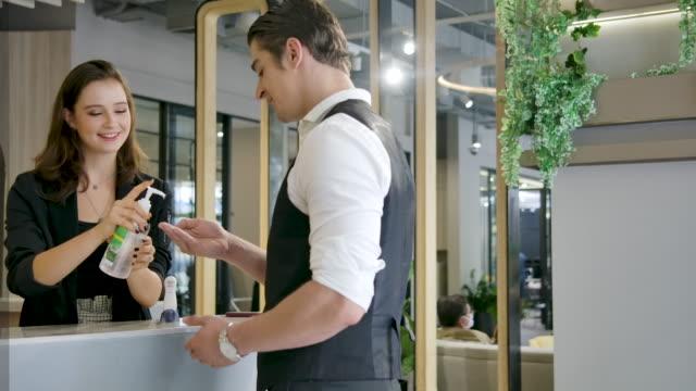 体温を測るホテル受付として働く若い女性。 - 受付係点の映像素材/bロール