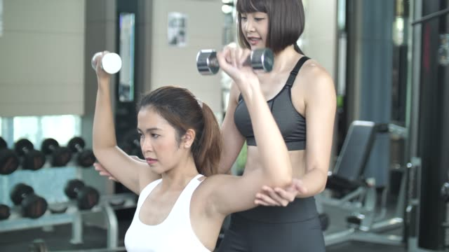 Young woman athlete is doing weight training with help of trainer in gym