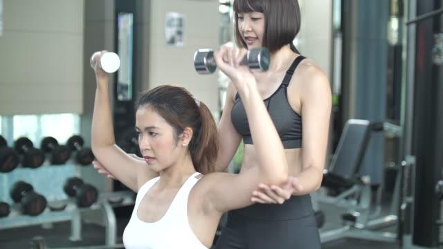 stockvideo's en b-roll-footage met jonge vrouw atleet doet krachttraining met behulp van trainer in de sportschool - grote borstspier