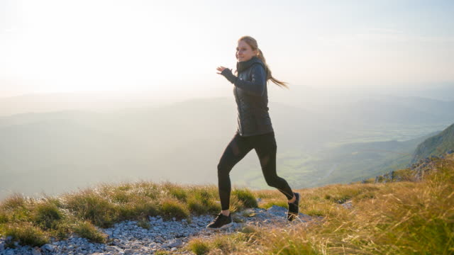 Young woman athlete running up a mountain