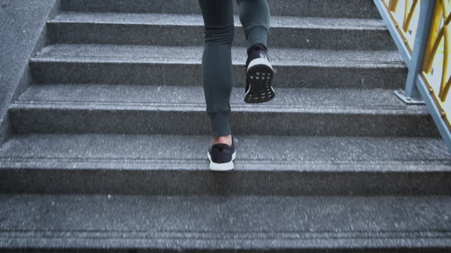 slo mo young woman athlete running up the stairs - steps stock videos & royalty-free footage