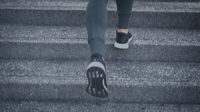 vídeos de stock e filmes b-roll de slo mo young woman athlete running up the stairs - degraus