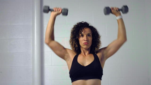 Young Woman Athlete Working Out with Dumbbells