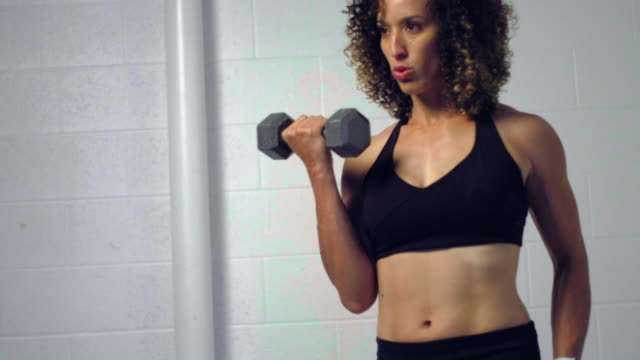 young woman athlete working out with dumbbells - bicep stock videos & royalty-free footage